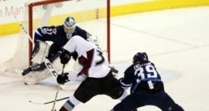 Toby Enstrom of the Winnipeg Jets and J.T. Compher of the Colorado Avalanche